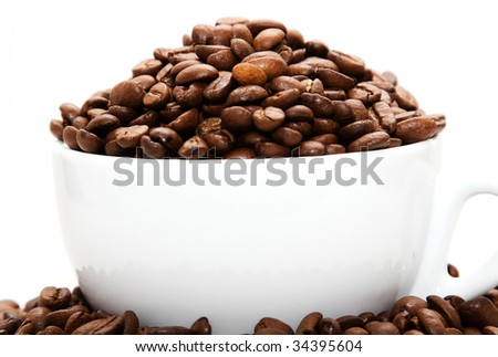 Mug filled with coffee beans - stock photo