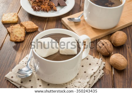 Mug filled with homemade hot chocolate, cookie with walnut on wooden table