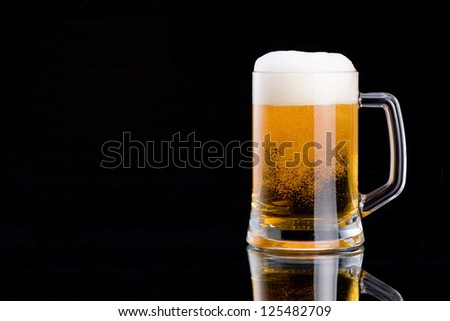Mug fresh beer with cap of foam on a black background - stock photo