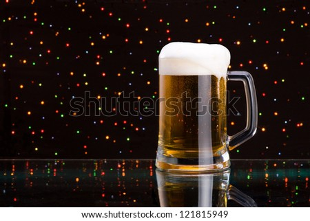 Mug fresh beer with cap of foam on colored light background - stock photo