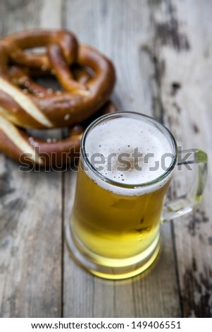Mug fresh beer with pretzels on wooden table  - stock photo