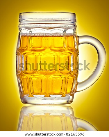 Mug full of beer on a golden background with reflections