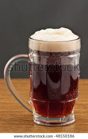 Mug of amber beer on wooden counter - stock photo