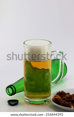 Mug of beer and green beer bottle empty bottle hors d'oeuvres on white background. - stock photo