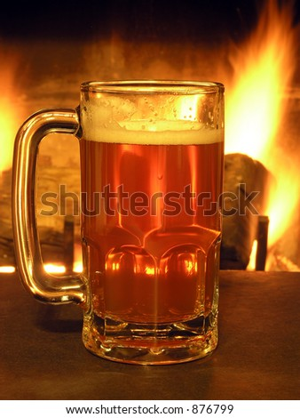 Mug of beer backlit by flames from fireplace