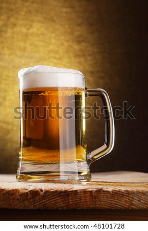 Mug of beer close-up on the wood table - stock photo