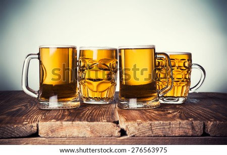 Mug of beer, on a wooden background - stock photo