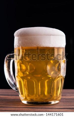 Mug of beer on black background - stock photo