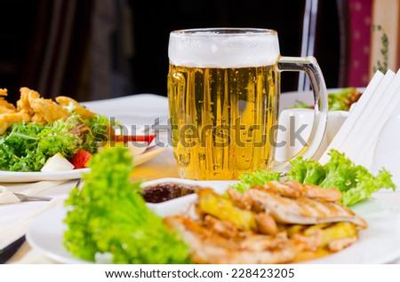 Mug of Beer on Restaurant Table with Plated Food Dishes - stock photo