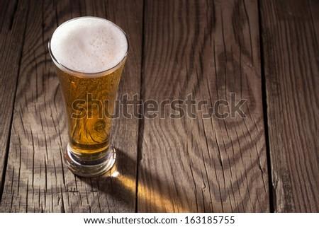 Mug of beer on wooden background  - stock photo