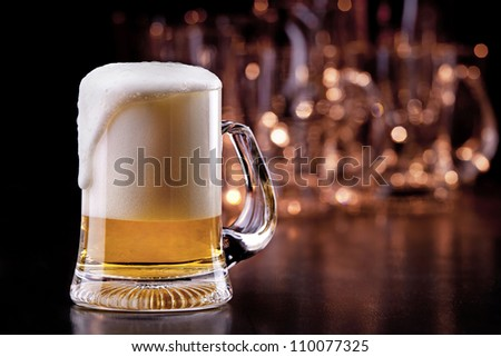 Mug of beer on wooden table - stock photo