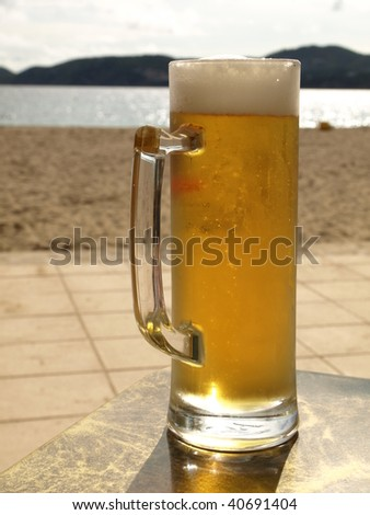 Mug of beer with a seaside view.