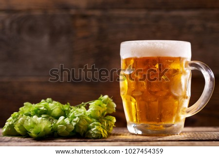 Mug of beer with green hops on wooden background