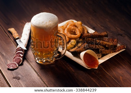Mug of beer with snacks on wooden table - stock photo