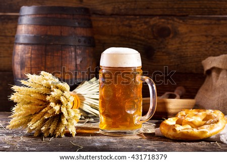 mug of beer with wheat ears and pretzel  on wooden background - stock photo