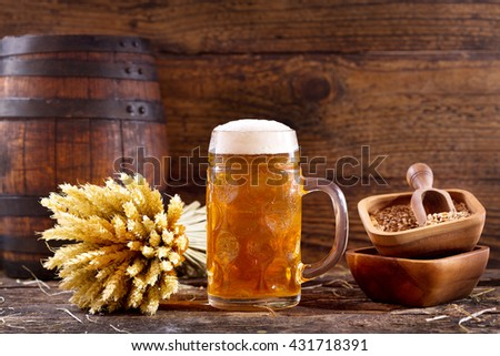 mug of beer with wheat ears on wooden background - stock photo