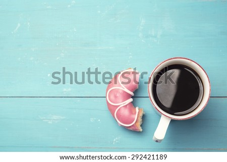 Mug of coffee and donut on wooden desk vintage - stock photo