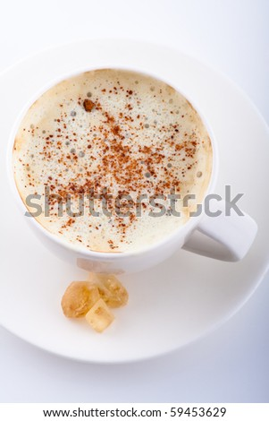mug of coffee with whipped cream, cinnamon and caramel sugar - stock photo