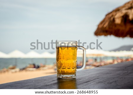 Mug of cold beer with foam on the table. Against the background of the sea. The Restaurant - stock photo