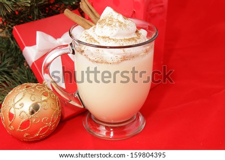 Mug of delicious eggnog, topped with whipped cream, nutmeg, and cinnamon sticks, for Christmas.   - stock photo