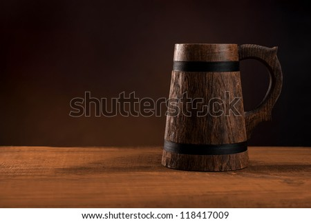 Mug of fresh beer on a wooden table. - stock photo