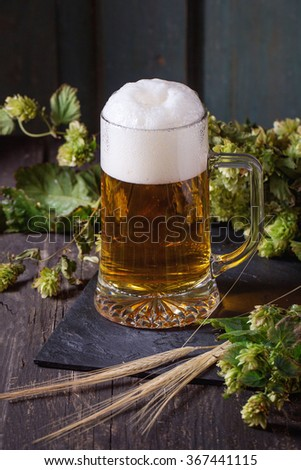 Mug of fresh draught lager beer with foam on black slate, served on old wooden table with green hop and ears of barley. Dark rustic style - stock photo