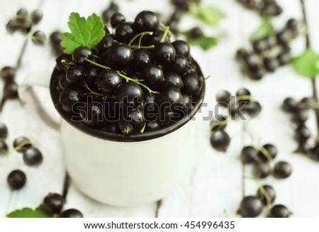 Mug of fresh ripe sweet blackcurrants on wooden background, selective focus - stock photo