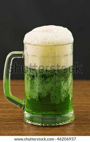 Mug of green beer on wooden counter - stock photo