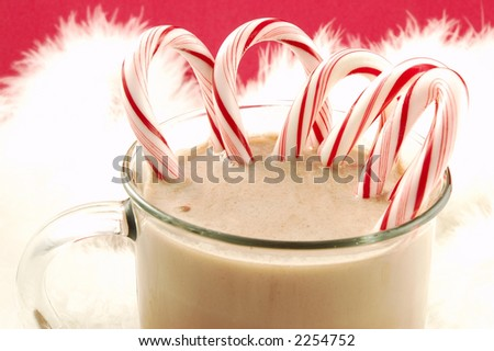Mug of hot Christmas cocoa with sweet candy canes isolated on a red background