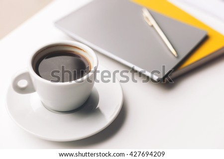Mug of hot drink and writing-pads on desk