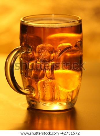 Mug of lager beer with bubbles on yellow