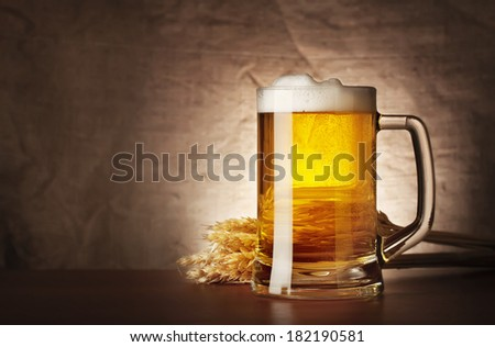 Mug of lager beer with spikelets on burlap background