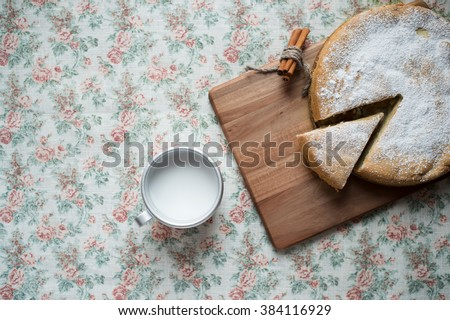 Mug of milk and homemade apple pie with red apples and cinnamon sticks on a rustic tablecloth. - stock photo