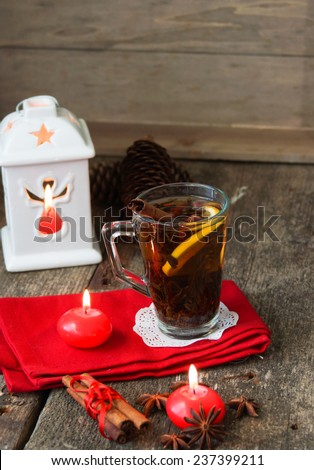 Mug of tea and orange on the table with christmas time decoration - stock photo