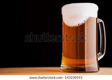 Mug with beer on dark background - stock photo