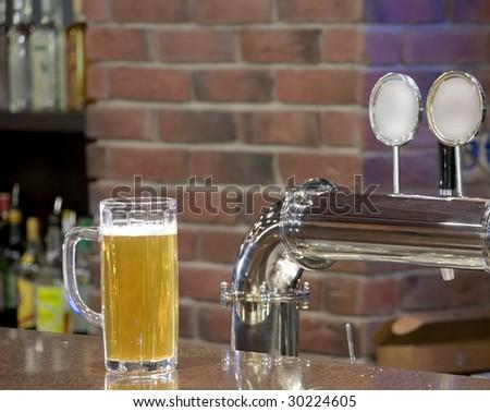 Mug with beer on the bar rack - stock photo