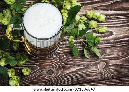 Mug with Beer with hop on a wooden table. focus on beer froth - stock photo