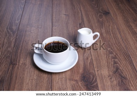 Mug with black coffee and milk jug on the wooden background - stock photo
