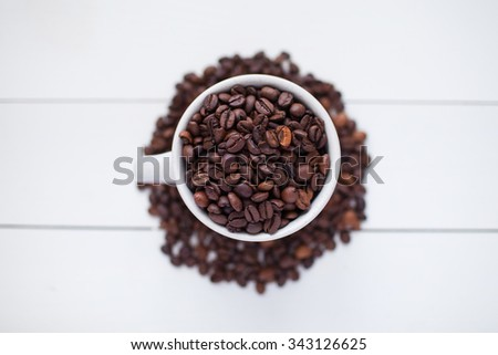 mug with coffee beans on a white wooden table