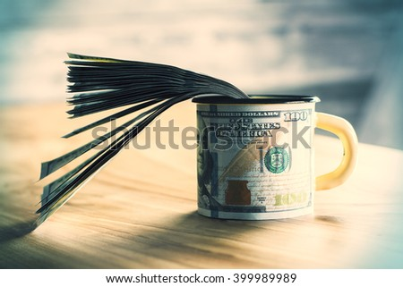 Mug with dollar print and banknote stack in it on wooden surface - stock photo