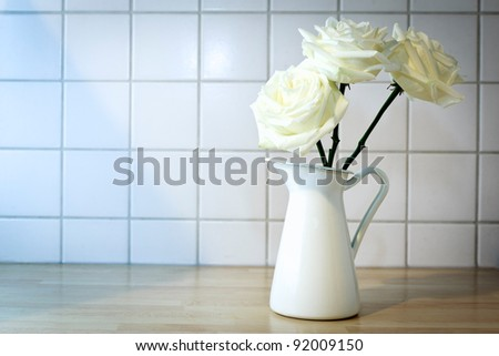Mug with roses on a countertop in front of white tiles. - stock photo