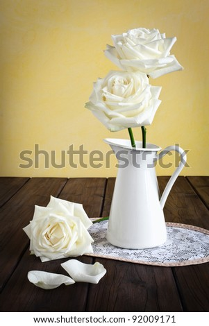 Mug with roses on a doily placed on a wooden background. - stock photo