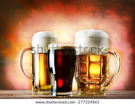 Mugs and a glass of beer on a wooden table on a red background