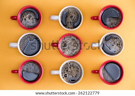 Mugs of black coffee in alternating red and white colors in an order placed for an office of business people viewed from above on an orange background - stock photo