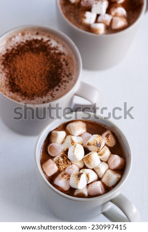 Mugs of hot chocolate cocoa drink, comforting cozy delicious milky mocha topped with roasted toasted marshmallows - stock photo