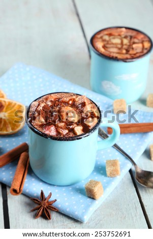 Mugs of hot coffee with marshmallow on napkin with lump sugar, cinnamon, star anise and dried orange on color wooden table background - stock photo