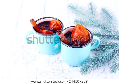 Mugs of mulled wine with pieces of orange and spice on snow covered background - stock photo