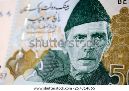 Muhammad Ali Jinnah, founder of Pakistan, printed on a used Pakistan banknote for 500 Rupees.  Image taken at an angle, less than 80% of note showing. - stock photo