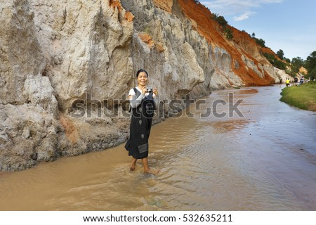 Mui Ne, Phan Thiet city, Vietnam - November 27, 2016 : Woman so excited to be walking on feet in the Red Stream ( it also named Fairy Stream) located near the beach of Mui Ne, Binh Thuan Province