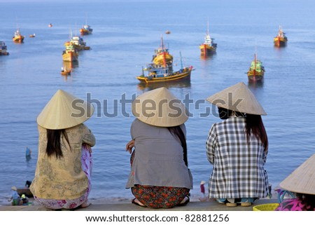 MUI NE, VIETNAM - APRIL 16: Unidentified women await returning fishing boats in Mui Ne, Vietnam at sunrise on April 16, 2011.  Vietnam seafood export is expected to reach $6.5bl USD by 2015. - stock photo
